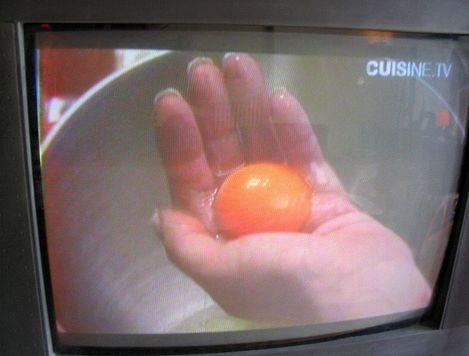 Main de Nigella Lawson contenant un jaune d'oeuf cru